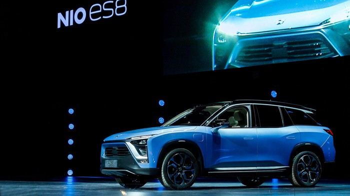 A blue NIO ES8, a seven-passenger battery-electric SUV, on an auto show stage.