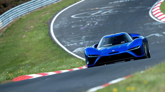 A blue NIO ES9, a low-slung electric sports car, is shown on a racetrack.
