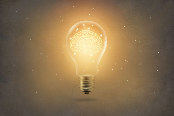 Golden brain glowing inside a light bulb on paper texture background