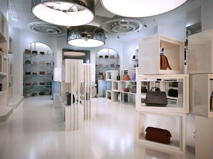 Luxury handbag store with shelves and products on display.