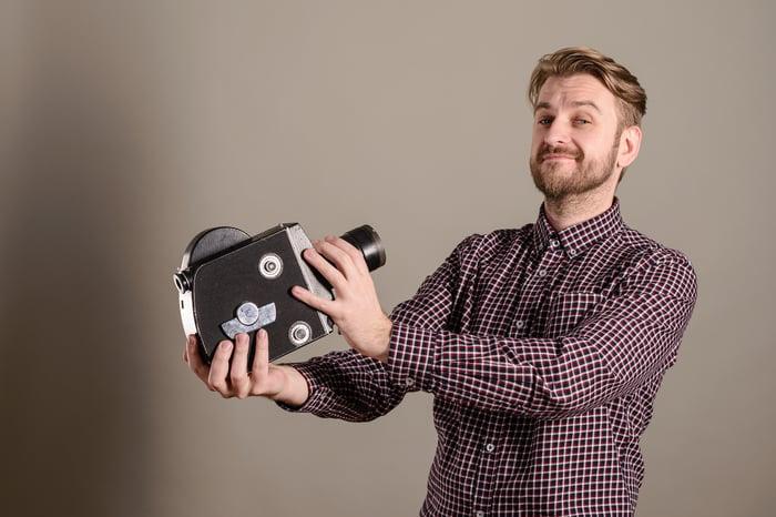 Man pointing movie camera at self