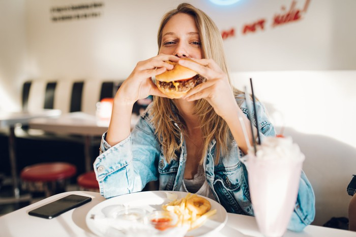 A woman sitting at a restaurant table eating a hamburger, french fries, and a milkshake.