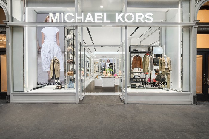 Kors storefront with gray trim and bright white interior.
