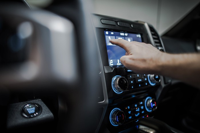 A hand reaches to operate an in-car dashboard multimedia system.
