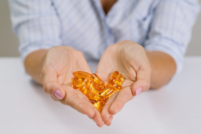 A person holds fish oil pills in her hand.