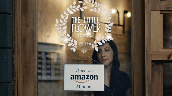 A woman stands in front of a sign touting that her store is open 24 hours on Amazon.