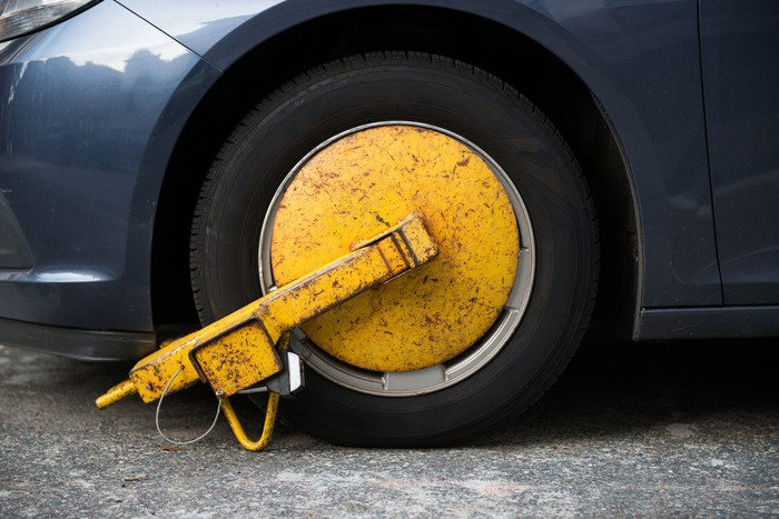 A yellow metal boot on the wheel of a car