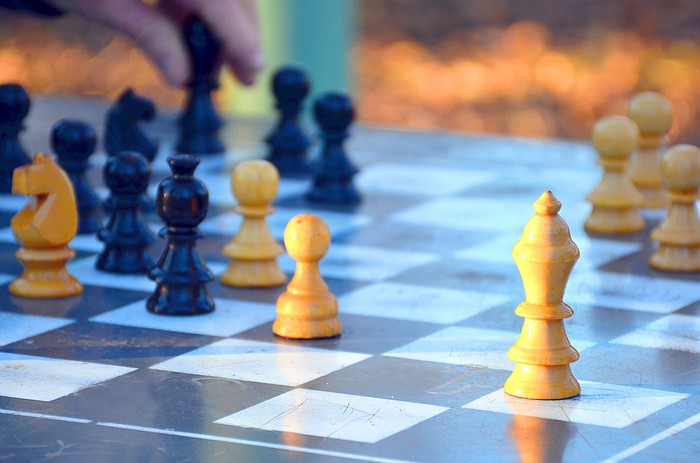 A chessboard with a hand moving a chess piece
