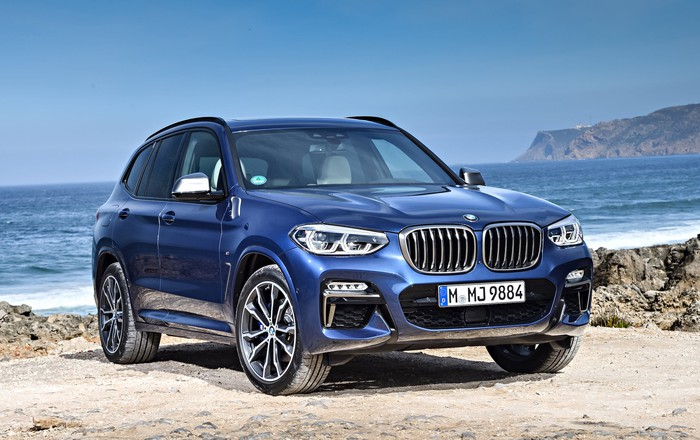 A blue 2018 BMW X3 SUV, wearing European license plates, parked on a rocky beach.