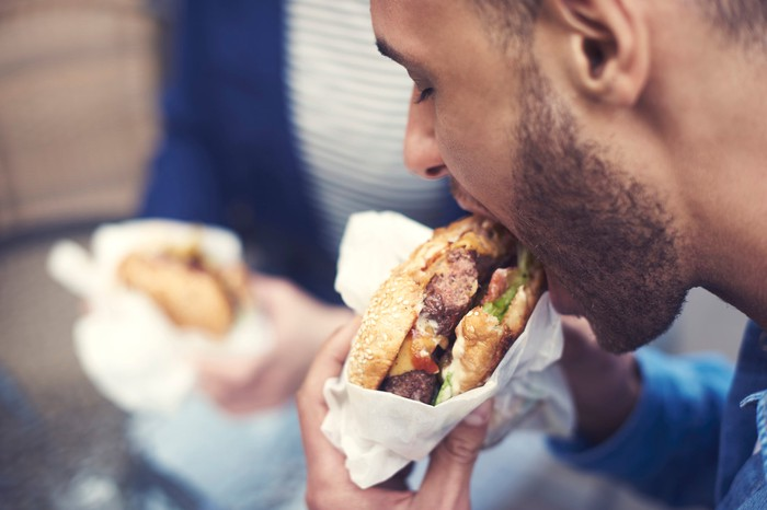 A close-up shot of a man taking a bite out of a hamburger.