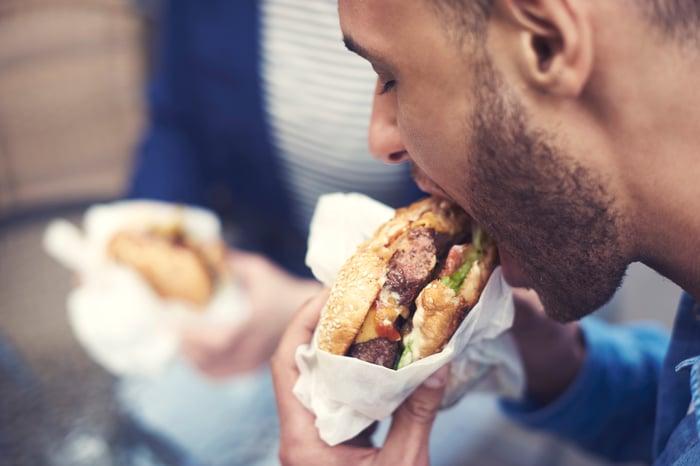 A close-up shot of a man taking a bite out of a hamburger.