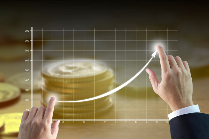 Businessman's hands touching two points on a chart that is rising quickly with coins in the background.