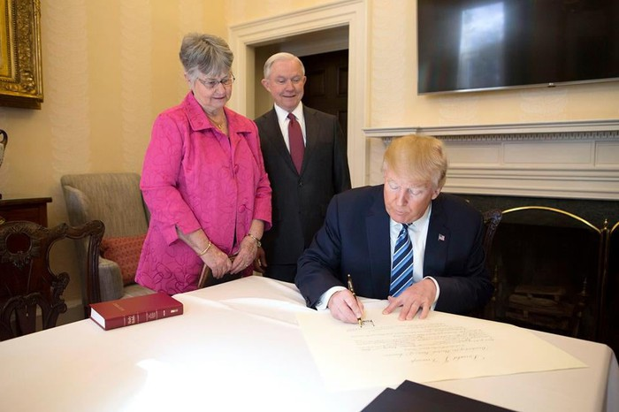 President Trump signing paperwork, with Attorney General Jeff Sessions and his wife to his right.