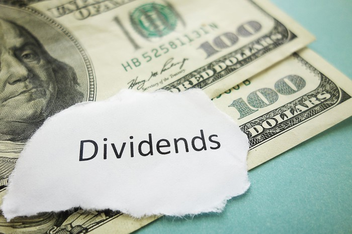"$100 bills sitting under a paper with the word ""Dividends"" on it."