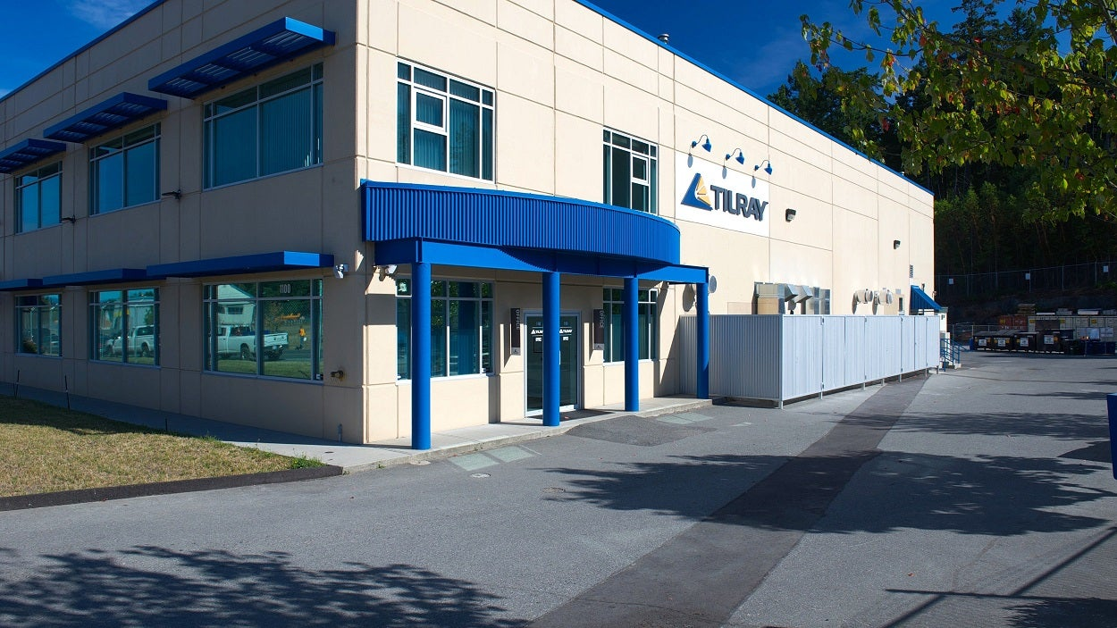 Building with Tilray logo on it, with parking lot and small lawn.