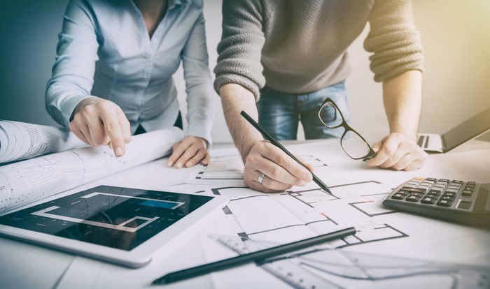 Man and woman with blueprints, tablet, laptop, and calculator, planning home construction