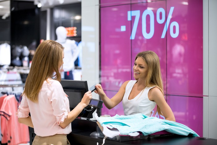 Woman in clothing store handing card to cashier
