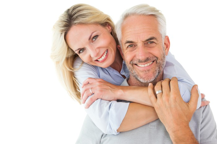 Older couple smiling and embracing.