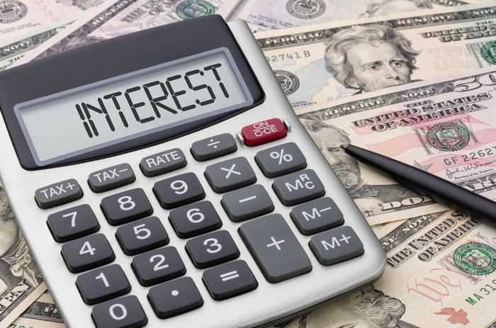 """Calculator that says """"interest"""" on its display, surrounded by money."""