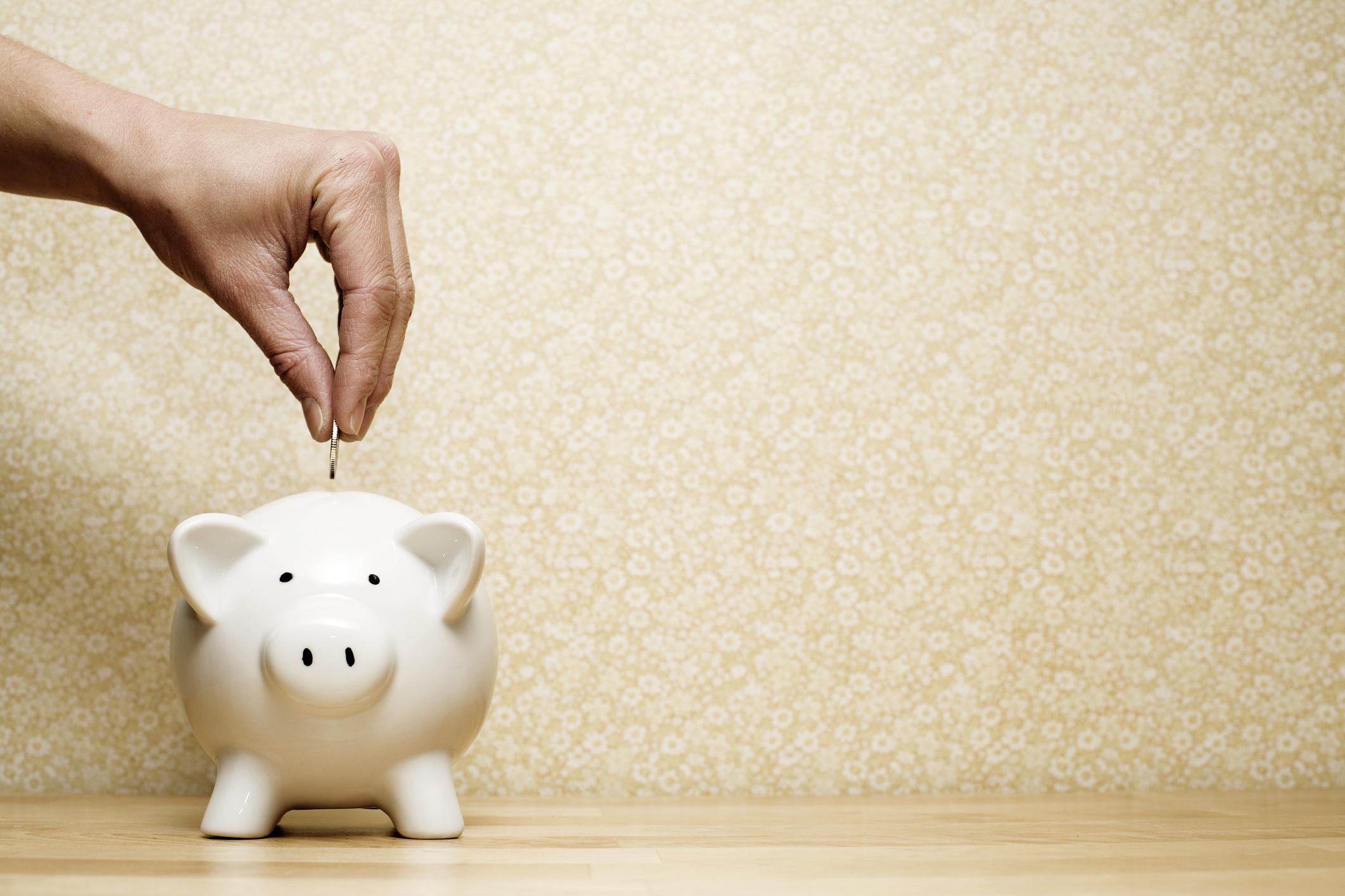 Person dropping a coin into a white piggy bank