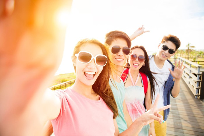 A group of young people take a selfie.