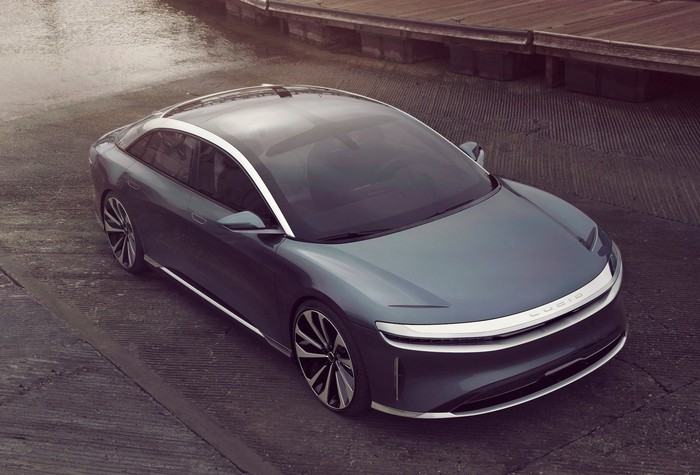 A gray Lucid Air, a sleek and futuristic electric luxury performance sedan, viewed from above.