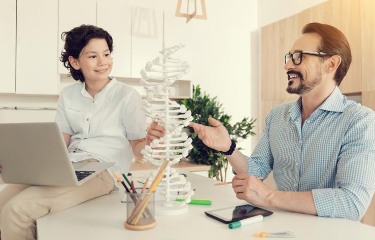 A man teaching a child about a DNA model.