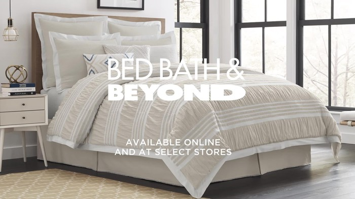 Large bed with many pillows in front of multiple windows, with Bed Bath & Beyond logo.
