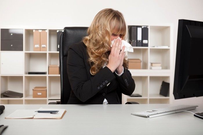 Woman blowing nose at her desk