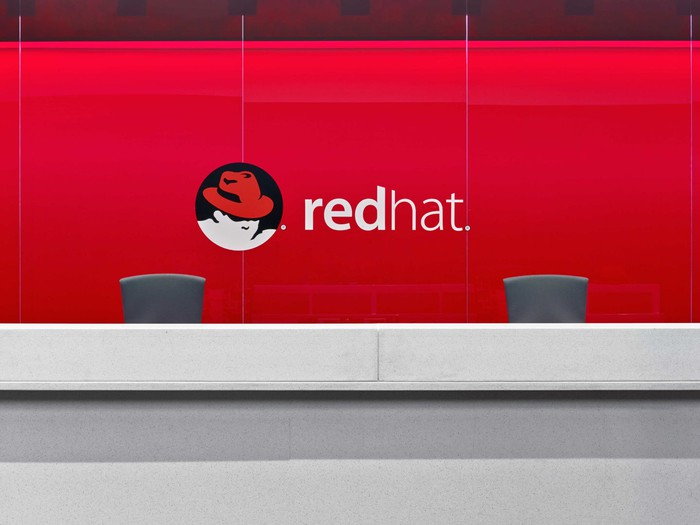 The front desk at Red Hat's Raleigh headquarters, featuring the corporate logo on a bright red wall.