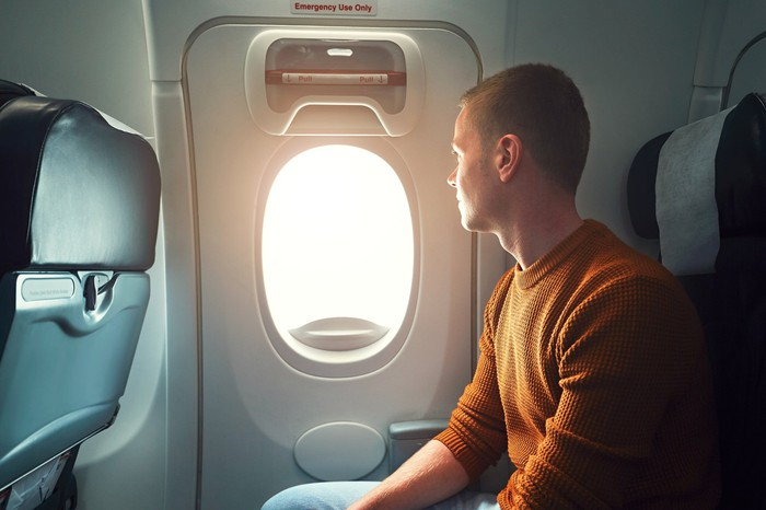 A man looking at an airplane's window exit