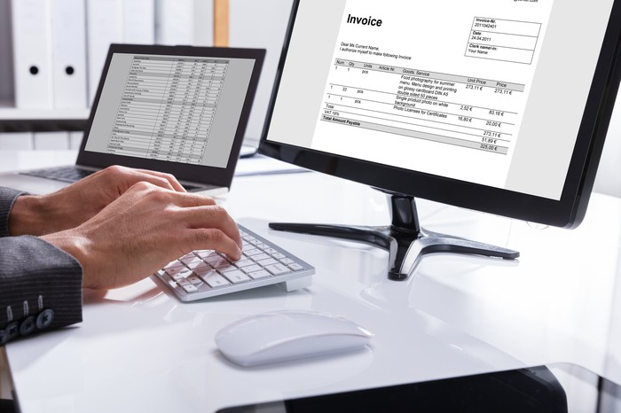 A businessman types an invoice on a computer.