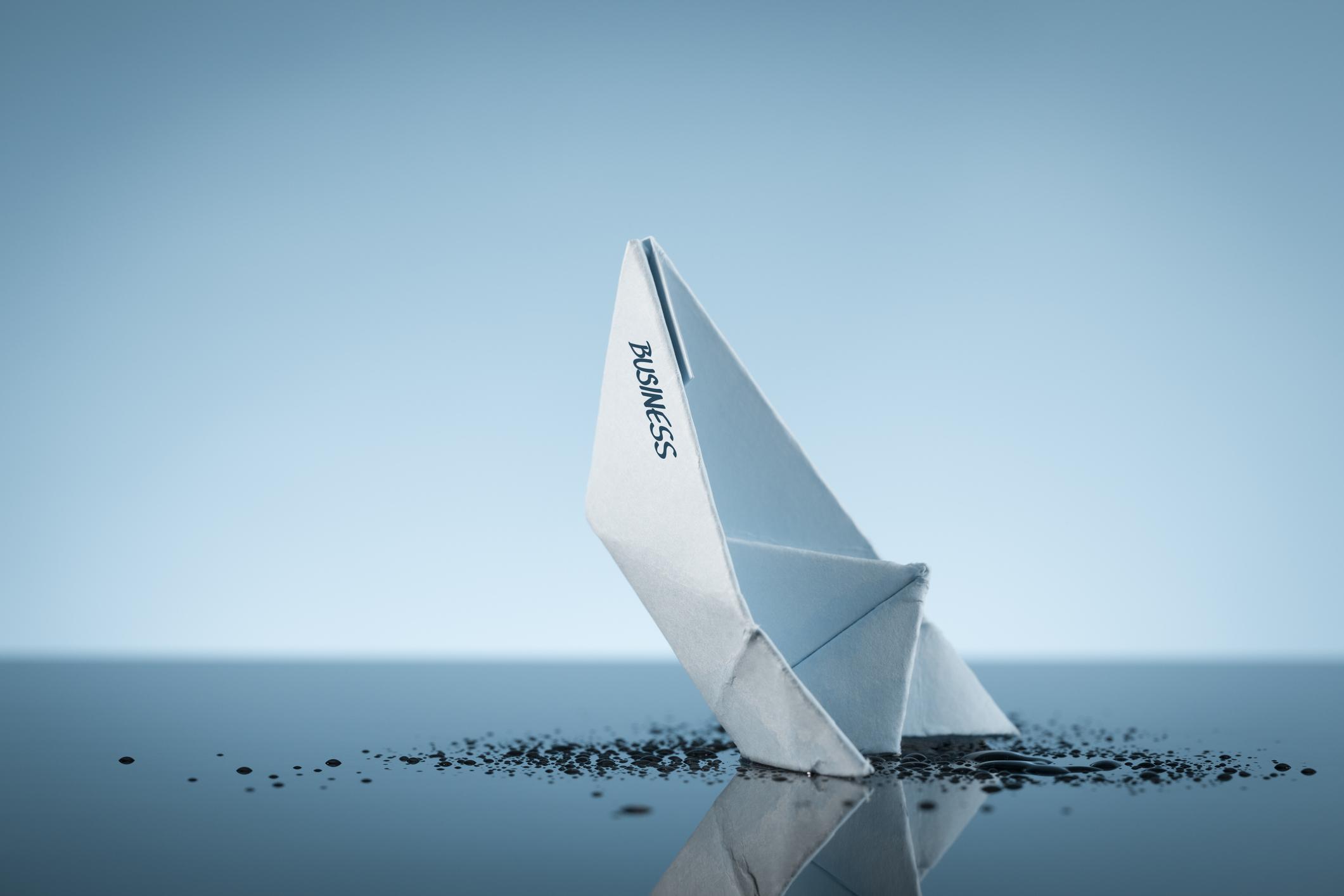 Paper boat sinking into a black liquid.