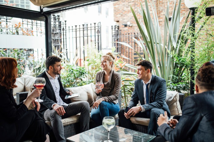 Group of professionally dressed adults sitting around having drinks