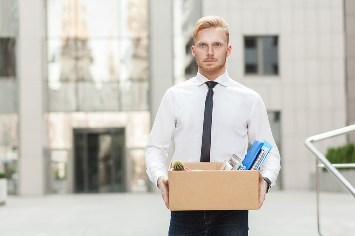 Man in dress shirt and tie carrying cardboard box of office supplies.