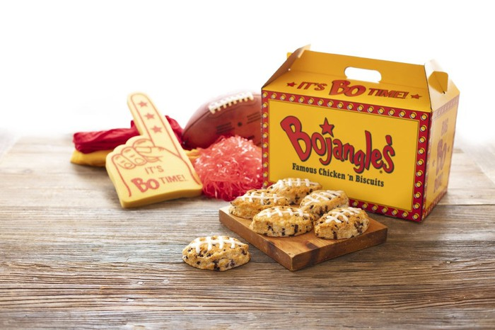 Box of Bojangles next to football-shaped biscuits, pompoms, a football, and a big-hand sign.