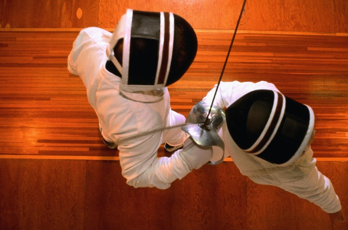 Two fencers locked in a close-up duel.
