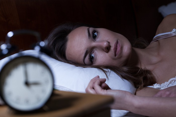 Woman lying awake in bed next to nightstand with clock.