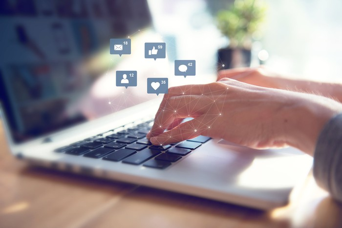 Hands typing on a laptop with social media icons floating above it.