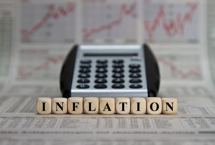 The word inflation spelled out by dice in front of a calculator and multiple rising charts in a newspaper in the background.