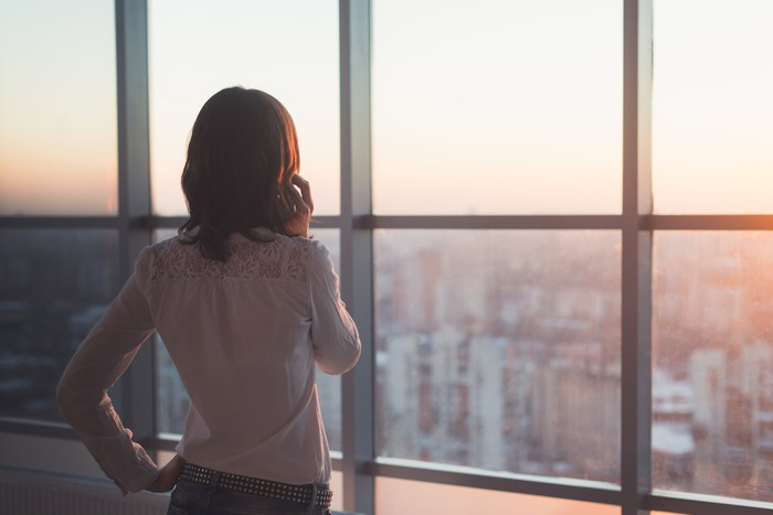 A woman stands by a window.
