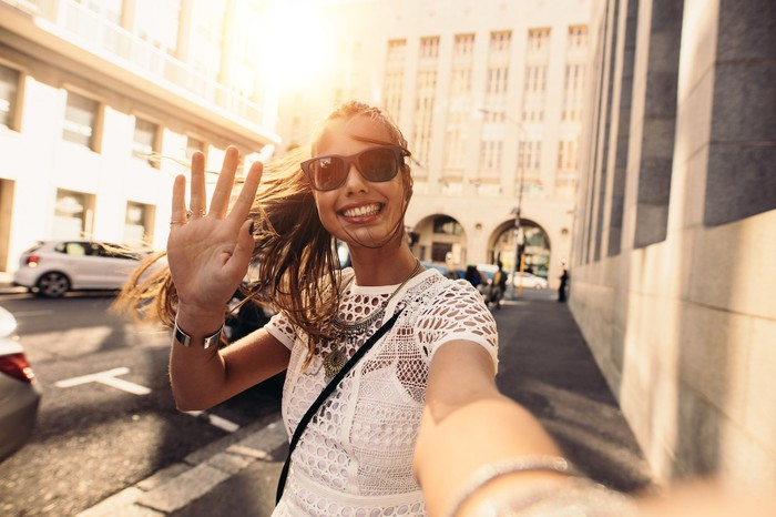 A young woman takes a selfie on a street.