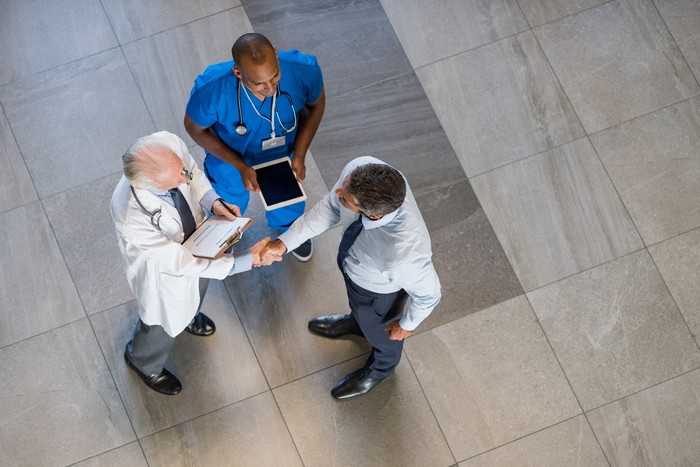 A doctor and a nurse talk with someone in a suit.