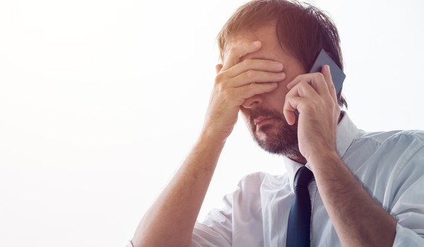 BUsinessman with hand over face talking on phone