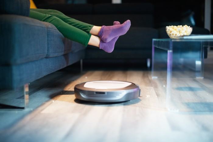 A robotic vacuum cleaner sweeps the floor.