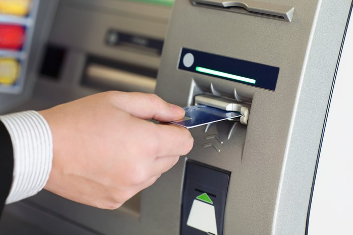 Hand inserting a card into an ATM