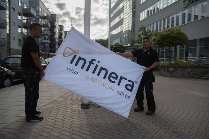 Two people on a sidewalk holding a sign with the Infinera logo and slogan.