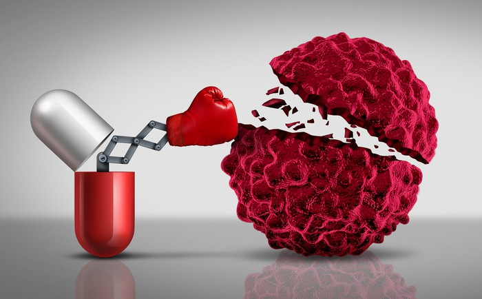 A red-and-silver cancer drug capsule punching and destroying a red cancer cell.