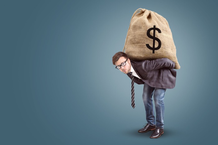A man carrying an oversized sack full of money on his back.