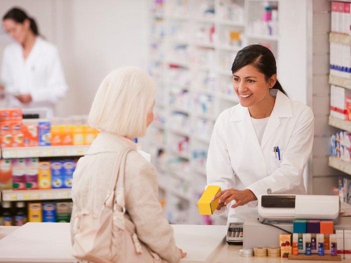 A pharmacist hands medication to another person.